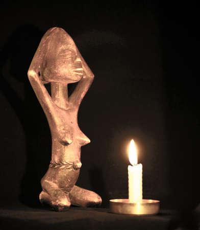 Figura de madera africana rezando junto a la vela en la oscuridad. Estilo retro