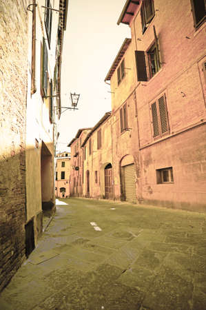 Narrow street in the medieval city of Siena in Tuscany