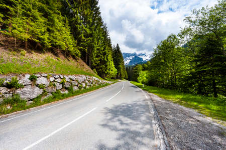 Winding asphalt road in Austrian landscape with forests, fields, pastures and meadows Stok Fotoğraf