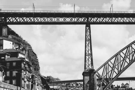 Bridge Built by Eiffel on the Bacground of the historical centre of the city of Porto with traditional Portuguese facades sometimes decorated with ceramic tiles of azulejo. Black and white photo