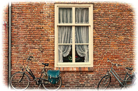 White window with Curtain and retro bicycles in the Dutch City. Bikes leaning against the red brick wall in Amersfoort. Vintage style toned picture