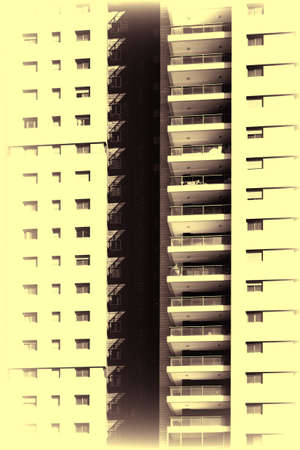 Facade of dwelling house with harmonic windows in a row. Windows and balconies of a multiroom apartment house of mass building in Israel. Vintage style toned picture