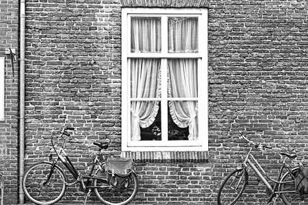 White window with Curtain and retro bicycles in the Dutch City. Bikes leaning against the red brick wall in Amersfoort. Black and white picture Stock Photo