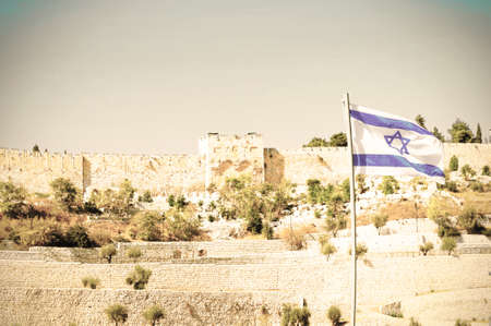 View from the Kidron Valley on the walls of the old city of Jerusalem and Israel flag. Retro style Standard-Bild