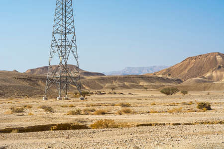 Electrical power lines on pylons in the landscape of the Middle East. Rocky hills of the Negev Desert in Israel. Breathtaking landscape of the rock formations.