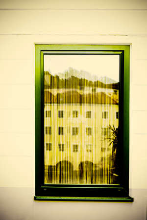 Typical windows of a house in a small town in Austria. Home in the Austrian city of Gmunden in a rainy day. Retro style Stock fotó