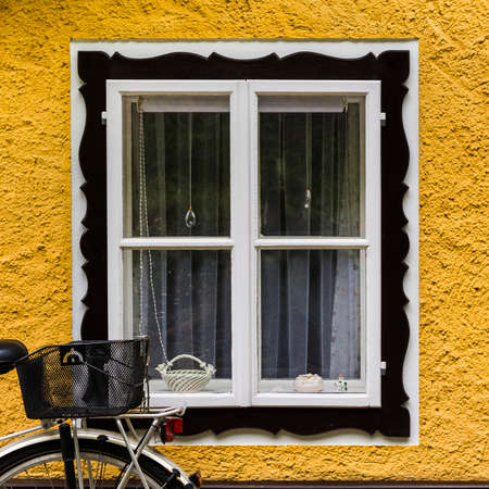 Bike at home in the Austrian city of Hallstatt on a rainy day. Typical window of a house in a small town in Austria.  Stock fotó