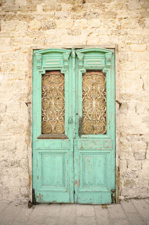 Ancient wooden door in old stones brick and cement wall in Jaffa. Vintage style.