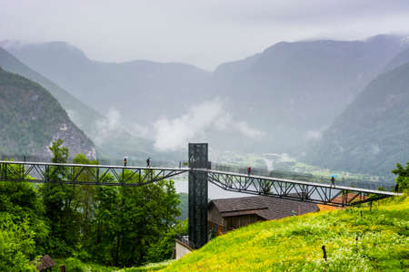 Morning mist, rain and clouds over the Austrian landscape with forests, mountains, pastures, meadows and villages.  View of the lake Hallstattersee in Austria through the pedestrian bridge