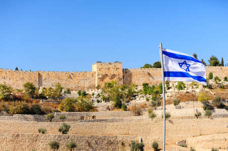 View from the Kidron Valley on the walls of the old city of Jerusalem and Israel flag