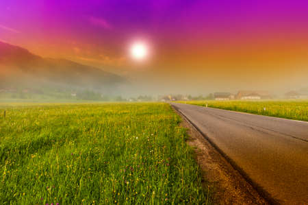 Morning mist over asphalt road in Austrian landscape with forests, fields, pastures and meadows at sunset