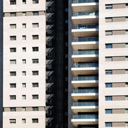 Facade of dwelling house with harmonic windows in a row. Windows and balconies of a multiroom apartment house of mass building in Israel