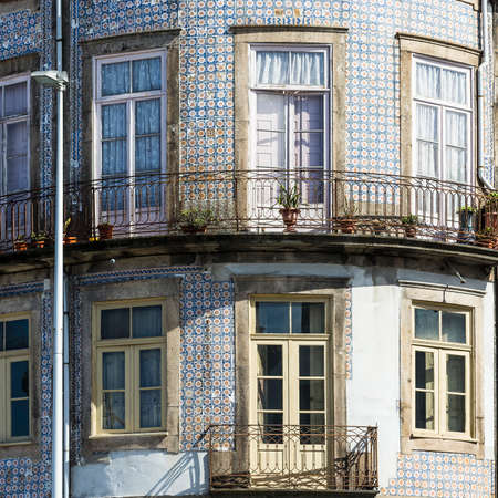 Traditional Portuguese ceramic tiles of azulejo decorate a facade of the old house in the city of Porto