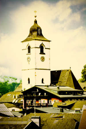 Pilgrimage Church located directly in the centre of St. Wolfgang in Austria.  Rain, morning mist and clouds over the  Austrian medieval small city. Retro style 免版税图像 - 150341219