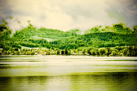 Rain and clouds on the Wolfgangsee in Austria. Morning mist over the Austrian landscape with lake, forests, fields, pastures, meadows and village. Vintage style 免版税图像 - 150340514
