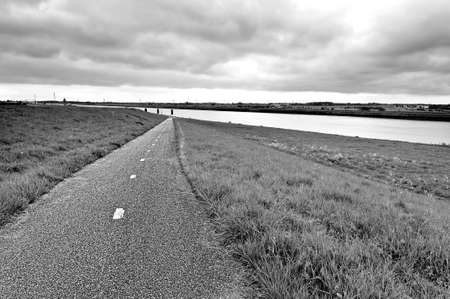 Agriculture on Land Reclaimed from the See in Netherlands. Asphalt road along protective dam and canal in Holland. Black and white picture