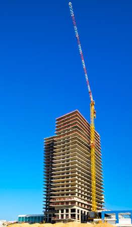 Crane and building under construction in Tel-Aviv. Industrial construction crane in Israel.