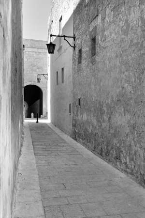Narrow street with traditional maltese buildings in historical part of Mdina. The city was founded as Maleth in around the 8th century BC by Phoenician settlers on the island of Malta. Black and white picture