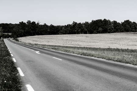 Asphalt road between autumn plowed fields in France after harvest Stock fotó