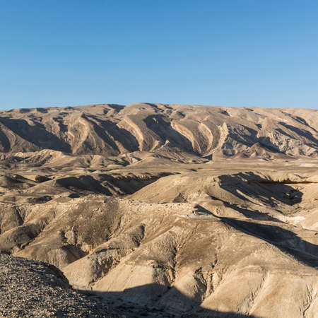 Rocky hills of the Negev Desert in Israel. Breathtaking landscape of the rock formations in the Southern Israel. Dusty mountains interrupted by wadis  and deep craters.
