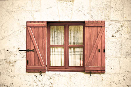 Wooden window with open shutters on the facade of a stone house in Spain. Retro style