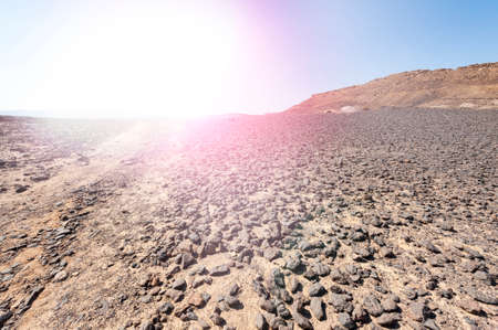 Hot afternoon sun of the Israel desert. Dusty mountains interrupted by wadis and deep craters.