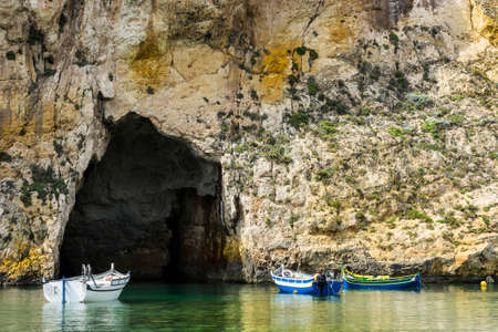 Pleasure boats at the rugged coastline delineated by sheer limestone cliffs, and dotted with deep caves on Malta. The Inland Sea is a lagoon of seawater on the island of Gozo linked to the Mediterranean Sea through an opening formed by a narrow natural arch. Stock fotó