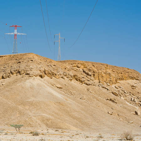 Desolate infinity of the Rocky hills of the Negev Desert in Israel. Electrical power lines on pylons in the landscape of the Middle East Banque d'images
