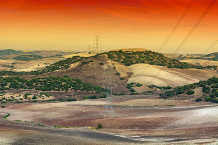 Olive grove and fields in Spain after harvesting at sunrise. Electrical power lines on pylons in the landscape of the Iberian Peninsula