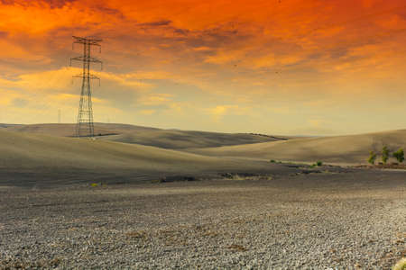 Olive grove and fields in Spain after harvesting at sunrise. Electrical power lines on pylons in the landscape of the Iberian Peninsula Banque d'images