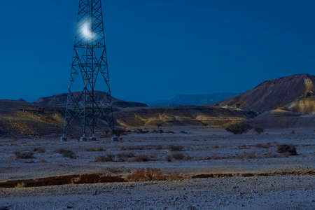 Electrical power lines on pylons in the landscape of the Middle East in the light of the moon. Rocky hills of the Negev Desert in Israel. Breathtaking landscape of the rock formations. Banque d'images