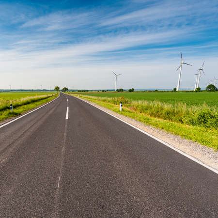 Asphalt road in Austrian landscape with fields, pastures, meadows and modern wind turbines producing energy. Vintage style