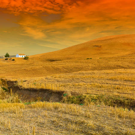Farmhouse on the field after harvesting at sunrise in Spain. Breathtaking landscape and nature of the Iberian Peninsula