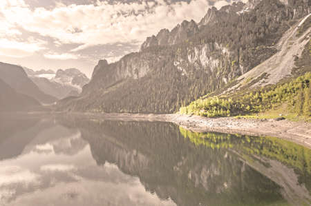 Austrian landscape with forests, meadows, fields and pastures surrounding the lake Gosausee on the background of Alps. Vintage style