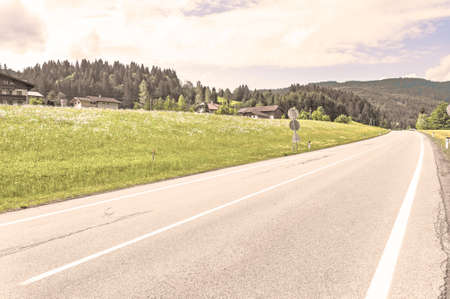 Asphalt road in Austrian landscape with forests, fields, pastures and meadows. Vintage style