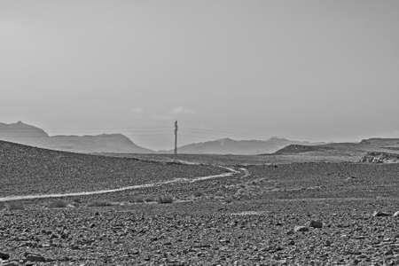 Electrical power lines on pylons in the landscape of the Middle East. Rocky hills of the Negev Desert in Israel. Breathtaking landscape of the rock formations. Black and white photography