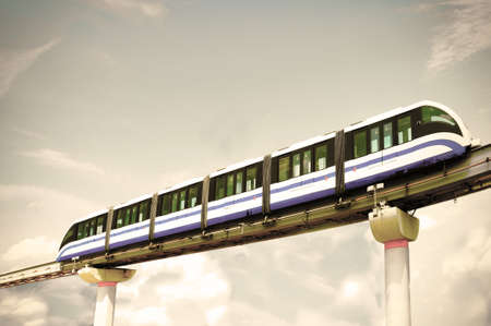High speed monorail train moves on railway girder against background of cloudy sky in Moscow, Russia. Retro style