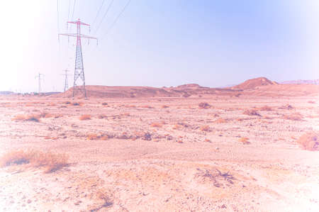 Electrical power lines on pylons in the landscape of the Middle East. Rocky hills of the Negev Desert in Israel in faded color effect Banque d'images