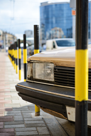 footway: Protective barrier made of yellow striped columns on road and car Stock Photo