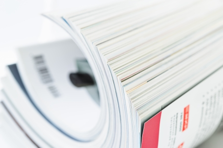Close-up of magazine pages on white background. Shallow DOF
