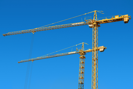 jib: Tower cranes on a blue sky background  Stock Photo