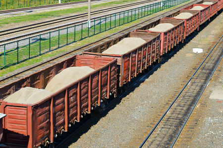 freight train: Rail freight wagons with sand Stock Photo