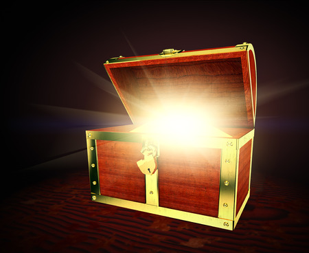 Old wooden treasure chest with strong glow from inside Standard-Bild
