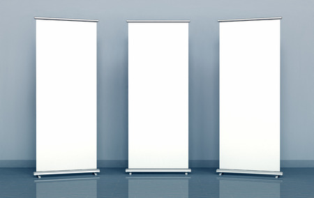 Blank roll-up banners against the blue wall Imagens