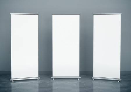 business banner: Blank roll-up banners against the grey wall Stock Photo