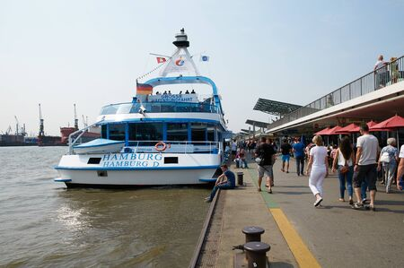 ferien: HAMBURG, GERMANY - AUGUST 14, 2015: Ferrys at Landungsbruecken jetty pier, Hamburg harbor