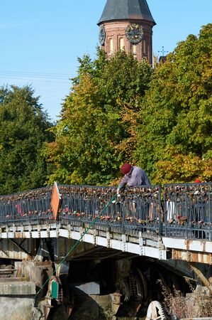 KALININGRAD, RUSSIA - OCT 15, 2015: Kant island, the old woman catches a fish from the  pedestrian bridge (Honigbrucke)