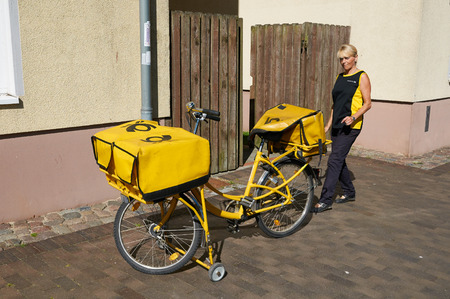 postal: STRALSUND, GERMANY - AUGUST 13, 2015: The postwoman with his yellow bike delivers the mail