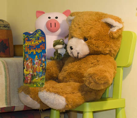 Green frog, bear and piglet are reading a story. photo