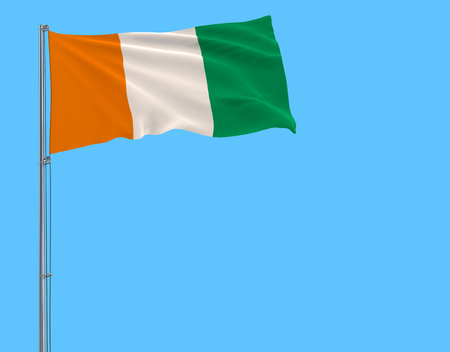 Flag of Cote dIvoire on flagpole fluttering in the wind on blue background, 3d rendering